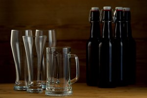 Beer glasses and beer bottles on a wooden background