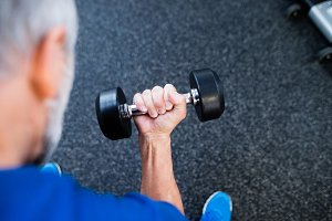 Unrecognizable senior man in gym working out with weights.