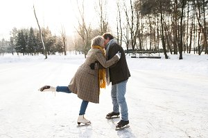 Senior couple in winter nature ice skating, hugging and kissing.
