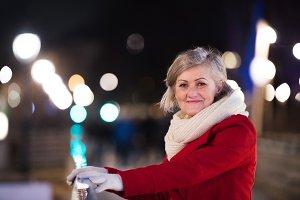Senior woman on a walk in night city. Winter