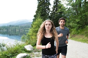 Beautiful young couple running at the lake in green nature.