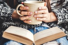 girl having a break with cup of fresh coffee after reading books or studying by Sergey Bogachuk in Education