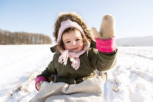 Cute little girl outside in winter nature, sitting on sledge