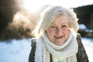 Beautiful senior woman on a walk, covered by snow