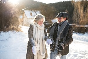 Beautiful senior couple blowing snow in sunny winter nature
