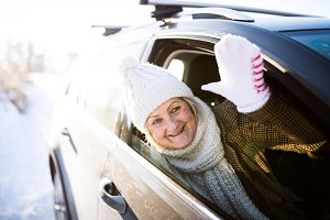 Senior woman in winter clothes in a car, waving