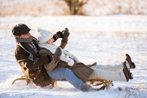 Beautiful senior couple on sledge having fun, winter day.