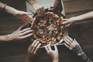 People Hands Reach for Pizza