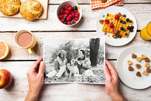 Hands holding picture of senior couple, breakfest meal. Studio s