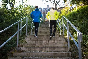 Two athletes running on stairs in sunny autumn, rear view.