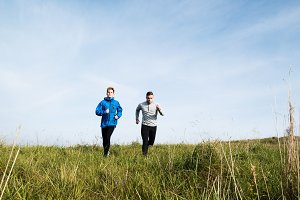 Two young hipster athletes running in sunny autumn nature