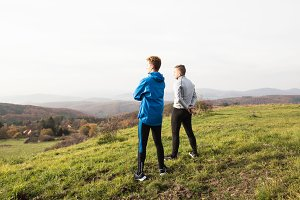 Two young hipster runners in sunny autumn nature restinng