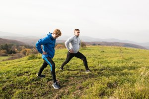 Two young hipster runners in sunny autumn nature stretching legs