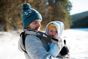 Father holding his son in baby carrier. Sunny winter nature.