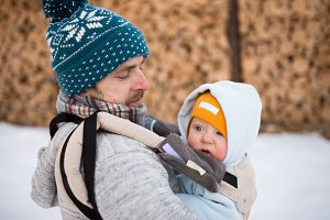 Father holding son in baby carrier. Winter nature.