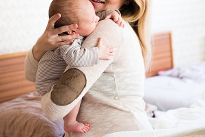 Beautiful young mother holding baby son in her arms