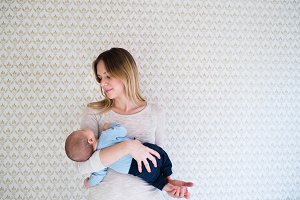 Beautiful mother holding baby son in her arms against wall