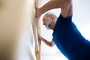 Senior man in gym exercising on wall bars.