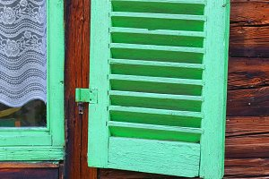 Green shutters on a wooden house