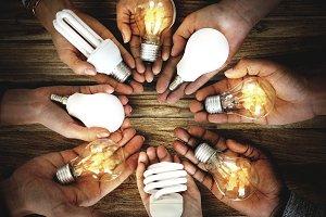 Hands holding light bulbs