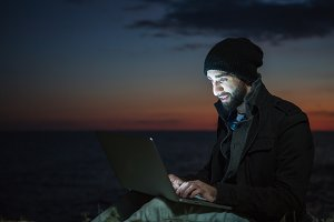 man uses his laptop at sunset