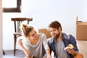 Young couple moving in new house, eating pizza.
