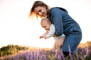 Young mother in nature with baby son in the arms.