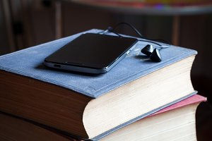 smartphone on top two vintage books