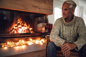 Mature man sitting by fire place