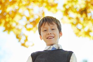 schoolboy laughing and playing in the autumn on the nature walk outdoors
