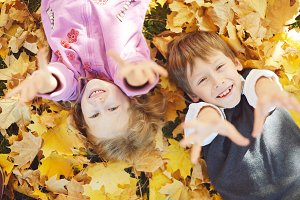 schoolboy and little girl laughing and playing in the autumn on the nature walk outdoors