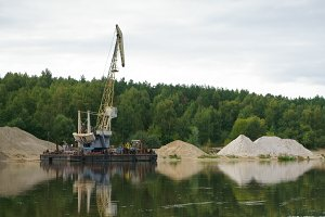 Floating crane and piles of sand