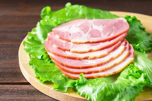 Sliced ham with fresh green lettuce leaves on a round cutting board. Meat products on a brown wooden table.