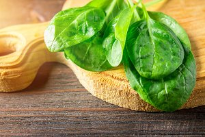 Green fresh spinach leaves on a wooden table