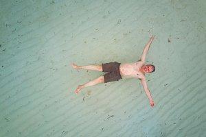 One adult man float on sea