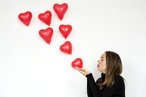 A woman blowing heart balloons