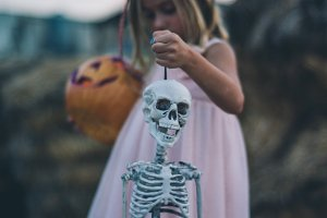 Blond girl blue eyes with skeleton halloween