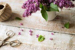 Purple lilac bouquet laid on wooden table. Studio shot.