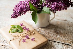 Purple lilac bouquet in vase and present laid on wooden table.