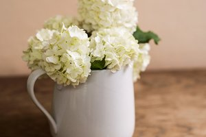 White lilac bouquet laid on wooden table. Studio shot.