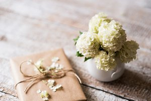 White lilac bouquet in vase and present laid on wooden table.