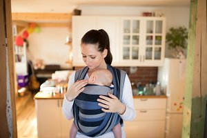 Beautiful mother in kitchen with her son sleeping in sling