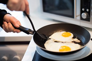 Unrecognizable man preparing fried eggs for breakfast. Close up.