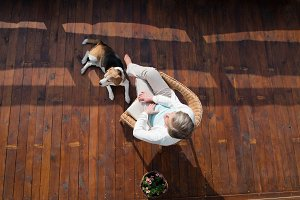 Senior woman with dog, sitting on wooden terrace, relaxing.