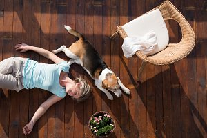 Senior woman with dog, lying on wooden terrace, relaxing.