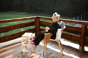 Senior woman on wooden terrace, resting with feet up.