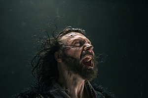 Portrait of a brutal bald-headed viking in a battle mail posing against a black background.