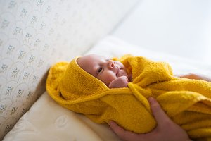 Unrecognizable mother drying her son with towel after a bath