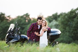 Couple in love standing at a motorbike. Green nature.
