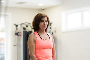 Senior woman in gym working out using kettlebells.